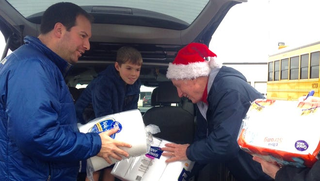 Chris Wortmann, left, and son Brady Wortmann, 8, of Farmington, unload items for the Stuff the Bus event in Victor Saturday with volunteer Wayne Brotsch.