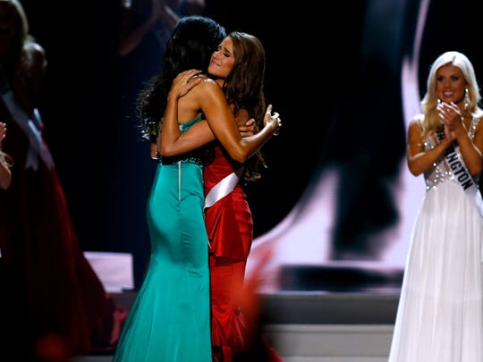 Miss North Dakota USA Audra Mari, left, and Miss Nevada USA Nia Sanchez embrace after Sanchez was announced the winner of the Miss USA 2014 pageant in Baton Rouge, La., Sunday, June 8, 2014. (AP Photo/Jonathan Bachman)