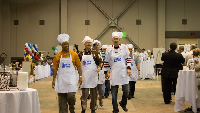 Manly chefs ready to cook at the 2014 100 Men Who Cook event by taking a lap around the room in the Chefs' Parade before settling in to whip up their own personal delicacies.
