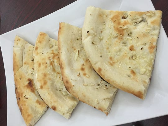 Fresh baked garlic naan was brought to the table.