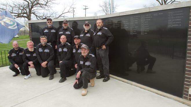 """Members of the Knights of the Road motorcycle club pose in front of the Michigan Riders Memorial Wall in Iosco Township. Kneeling, from left, are Larry """"Larry Love"""" Miller, Chuck Lodge, David """"Short Story"""" Spring, Kevin """"Knucklehead"""" Tamachaski, Jerry Wheeler and Don """"Crawdad"""" Crawford. Standing are, from left, Mark """"Twix"""" Harden, Rick """"CK"""" Mailloux, Kenny Kirby and President Mike """"Chop Chop."""""""