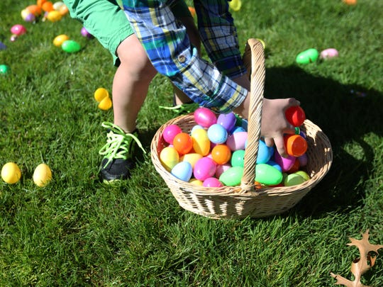 Griffin Robinson fills a basket with Easter eggs at