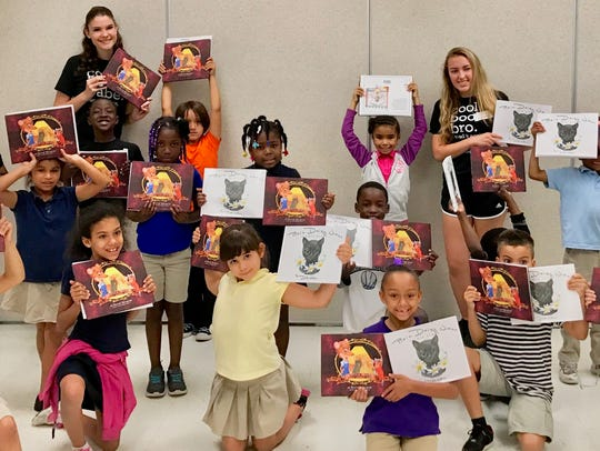 Second-grade students hold up books they received through