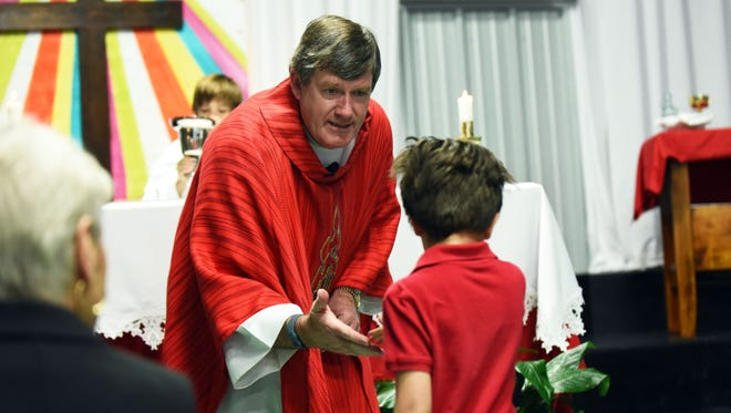 Father Tommy Conway welcomes children during a Palm Sunday mass at St. Fabian's temporary facility in the Benedict Day School.