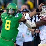 Oregon quarterback Marcus Mariota, left, pushes away Florida State safety Tyler Hunter during the first half of the Rose Bowl NCAA college football playoff semifinal game in Pasadena, Calif. There will be several noticeable absences when the three-day draft starts Thursday night, including potential top picks. Florida State quarterback Jameis Winston, Oregon's Mariota and Alabama wide receiver Amari Cooper all plan to skip the spotlight.