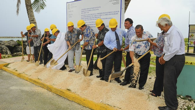 Gov. Eddie Calvo, center, and others participate in the ceremonial turning of soil during a groundbreaking ceremony at the Paseo de Susana in Hagåtña on Sept. 2. The ceremony was to kick off the construction of an ADA-compliant fishing and viewing platform to be built along the southern edge of the peninsula.