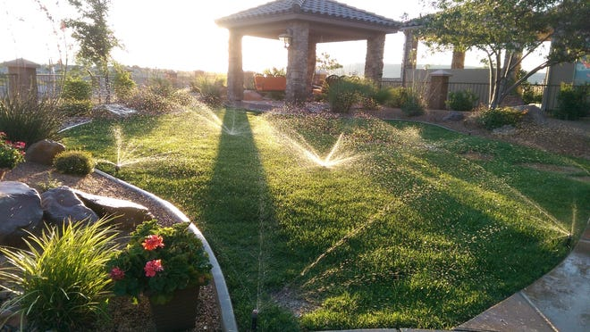Morning sun reflects through the sprinkler water at Jim and Carol Thalman's home in the SunRiver area of St. George.