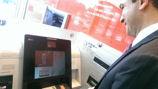 Bank of America executive Bassam Awadalla demonstrates how an Automated Teller Assist machine works at the bank's Kennett Square branch by video-chatting with Chrisine, a teller located at the bank's call center near Newark.