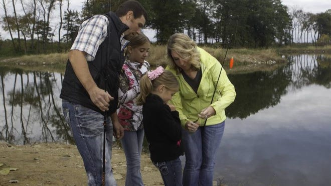 Amy Wilsdorf (green jacket) takes her family to a Discover Nature Fishing clinic at Busch Memorial Wildlife Conservation Area.