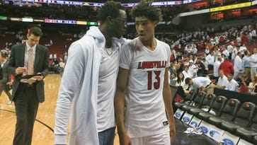 Louisville's Mangok Mathiang consoles teammate Ray Spalding after he and the rest of the Cards got hammered by Virginia Saturday afternoon at the KFC Yum! Center in downtown Louisville as Louisville lost 63-47. Spalding had 12 points and seven rebounds.