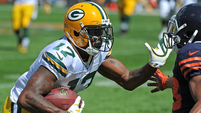 Green Bay Packers receiver Davante Adams (17) fends off a tackler after making a catch against the Chicago Bears at Soldier Field September 13, 2015