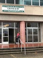 A woman leaves the Shasta County Courthouse as a grand jury-related banner hangs over the front entrance.