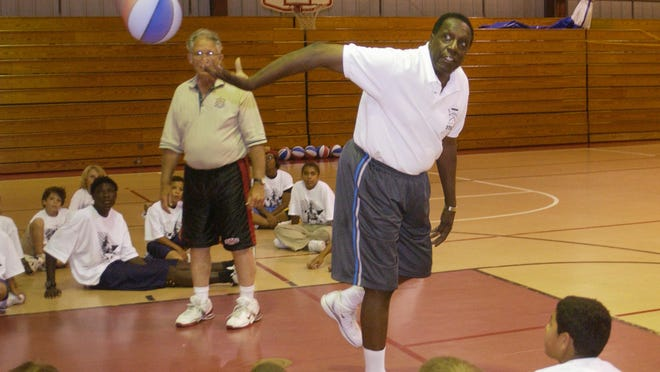 Meadowlark Lemon from the famed Harlem Globetrotters conducted a basketball camp at the Palm Bay Community Center in 2006. Here he is making a shot backwards for the kids.
