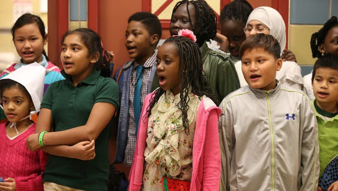 Sixth grader Rebecca Baraka, a native of the Republic of Congo, center, joins with schoolmates in singing a pair of Swahili songs they learned in music class during the Rochester International Academy's 5th annual Thanksgiving Dinner held at the school Monday, Nov. 23, 2015.