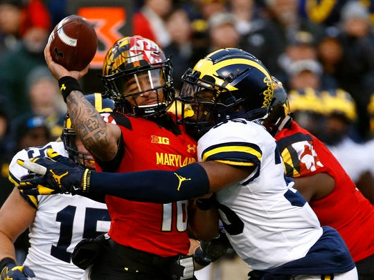 Michigan linebacker Josh Uche, right, tackles Maryland quarterback Ryan Brand as Brand throws an incomplete pass in the first half on Saturday, Nov. 11, 2017, in College Park, Md.