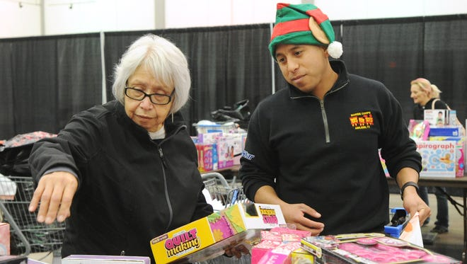 Gloria Soto, left, selects some toys for her granddaughters, ages 5 and 6, assisted by Gunnery Sgt. Victor Perez, right, during the annual Marine Corps Toys for Tots Thursday, Dec. 15, 2016. Toys were distributed with the help of the Salvation Army .