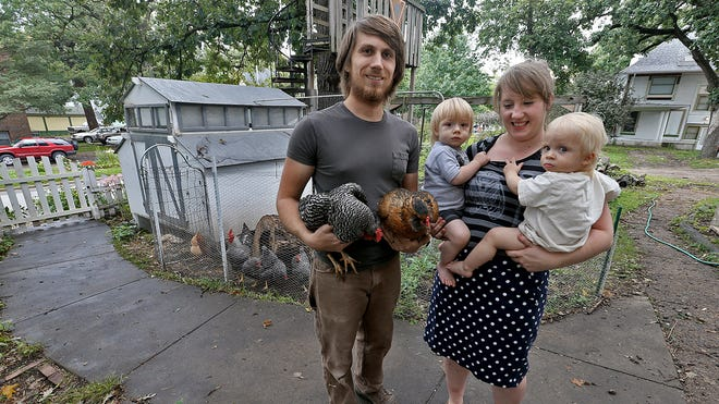 """Standing next to the chicken enclosure in the yard of their Drake neighborhood home, Grant Stuart, left, held two birds as his wife, Allison, holds their twin sons Ben, left and Theo. """"Chickens are easy,"""" Allison said of caring for the fowl. """"It's easier than having a dog."""""""