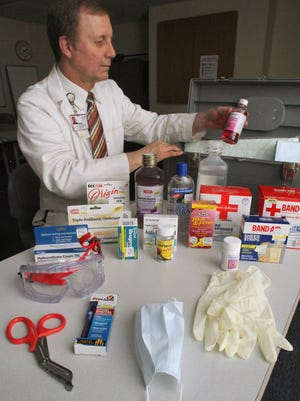 Pharmacy manager Jim Vander Linde shows off some of the common supplies recommended for use in a home medical kit. From front left to right by rows: surgical scissors, thermometer, standard paper masks, disposable gloves, safety goggles, diphenhydramine, hydrocortisone cream 1%, Ibuprofen, asperin, anti-diarrheal, acetominophen, band aids assorted sizes, triple antibiotic ointment, outdoor skin clenser (for poison oak and poison ivy oils), pediatric electrolyte fluis, aloe vera 100, sterile water for eye and wound irrigation-external use only, 4x4 gauze sponges and 4x4 gauze pads, benedryl liquid.