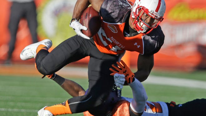 Nebraska running back Ameer Abdullah, top, runs the ball in the first half during the Senior Bowl NCAA college football game Saturday, Jan. 24, 2015, in Mobile, Ala. (AP Photo/Brynn Anderson)