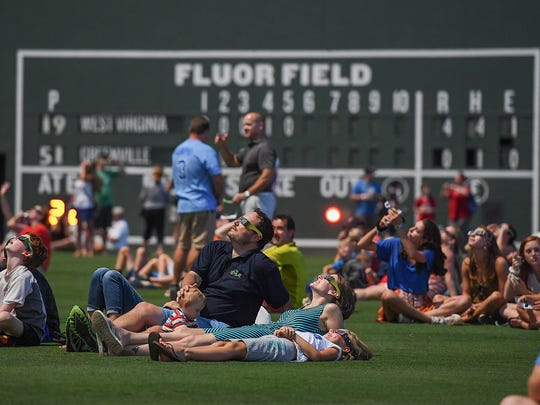 Greenville Drive fans sit in the outfield at Fluor Field at The West End when the game was paused for the solar eclipse on Monday, August 21, 2017.