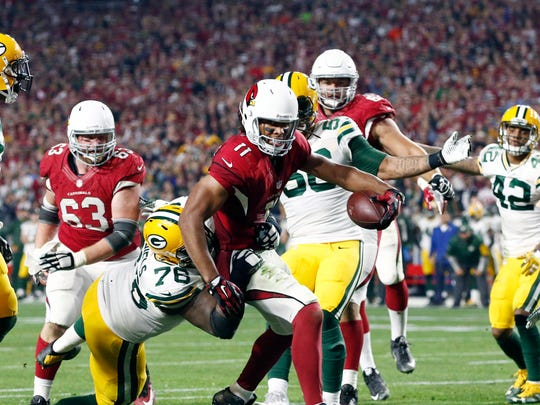 Cardinals wide receiver Larry Fitzgerald (11) scores the game-winning touchdown against the Packers during overtime Saturday in Glendale, Ariz.