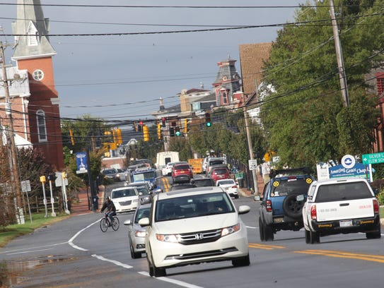 A cyclist rides across Route 299 near downtown Middletown