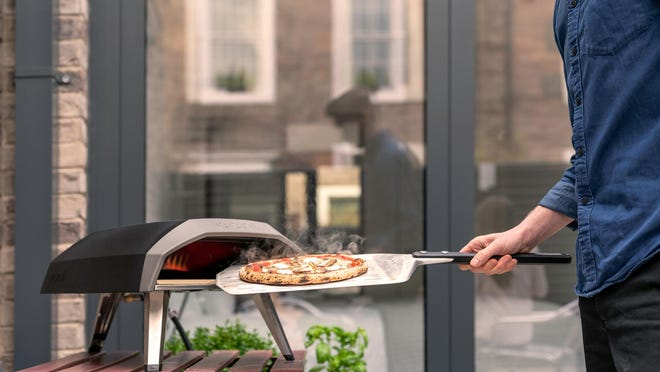 This photo provided by Riverbend Home shows the Ooni Koda propane pizza grill, that's ready to go in 15 minutes and cooks pizza in about a minute, as well as roasted fish, steak or vegetables.