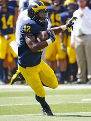 Wolverines running back Chris Evans runs the ball in