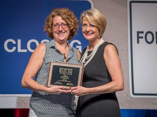 Pam Cook of FASTSIGNS of York, left,acceptsthe Silver Sales Award from Catherine Monson, CEO of FASTSIGNS International Inc.