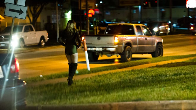 Potential johns circle an area known for prostitution in Houston. Pimps wait nearby in strip mall parking lots.