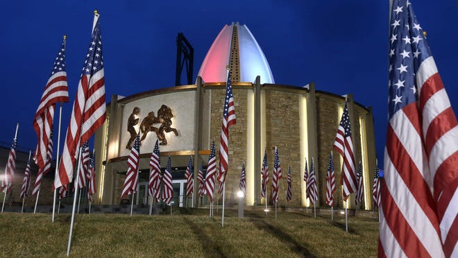 The Pro Football Hall of Fame is bathed in red, white and blue lights and surrounded by U.S. flags last year.