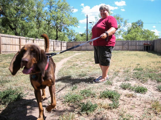 Tara Davis and her dog, Tracker, walk around Davis' backyard Thursday, July 20, in San Angelo. Davis received help purchasing her home through a local HUD-funded program.
