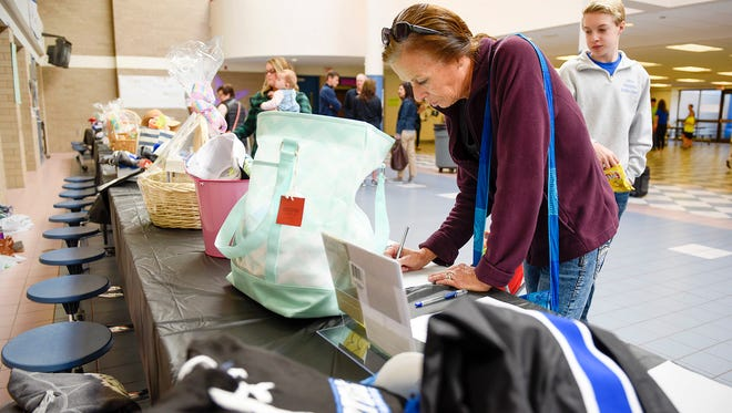 Cindy Lanin, Buffalo, places bids on some of the items in the silent auction during the Family Fun Fest Saturday, March 12, at the Sartell High School.