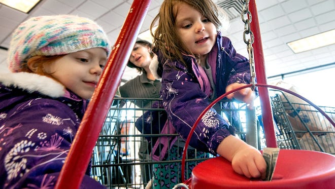 Olivia Dearborn, 4, right, of Elkton, Va., puts money in a Salvation Army Red Kettle with the help of her sister, Donna, 6, left, on Nov. 18, 2014.