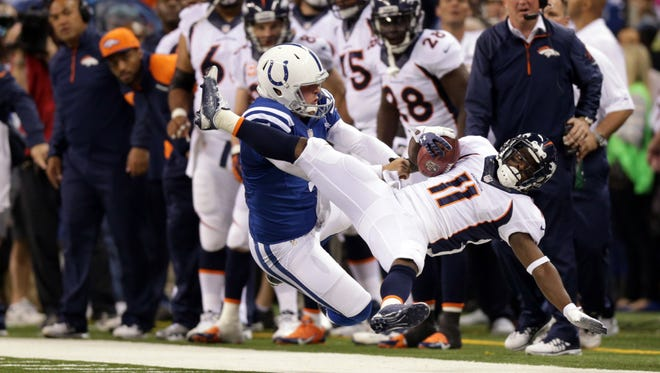 Indianapolis Colts punter Pat McAfee, #1, knocks Denver Broncos wide receiver Trindon Holliday, #11, off his feet.