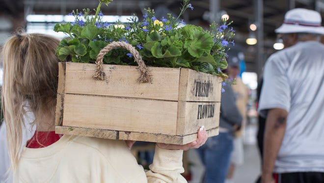 Shoppers carry heavy loads during Flower Day at Eastern Market in Detroit, Sunday, May 20, 2018.