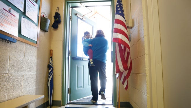 """Donna D'Angio carries her granddaughter Maggie, 2, after voting during the NY primaries at the United Church of Pittsford. """"Maggie is learning to vote"""" said Donna."""