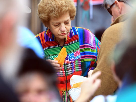 A woman eats a tamale during Tamale Fest on Saturday,