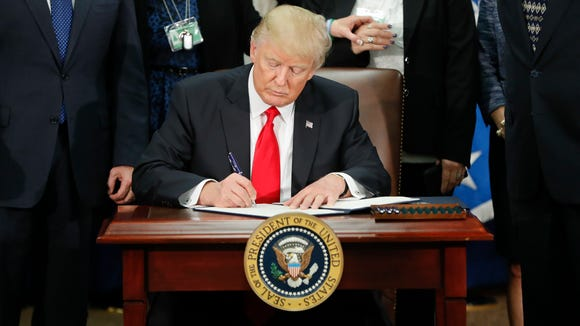 In this Jan. 25, 2017, photo, President Donald Trump signs an executive order for border security and immigration enforcement improvements at the Department of Homeland Security in Washington. Immigration to the United States has come in swells and dips over the past two-plus centuries, driven by shifts in U.S. policy, the mood in the country and world events.