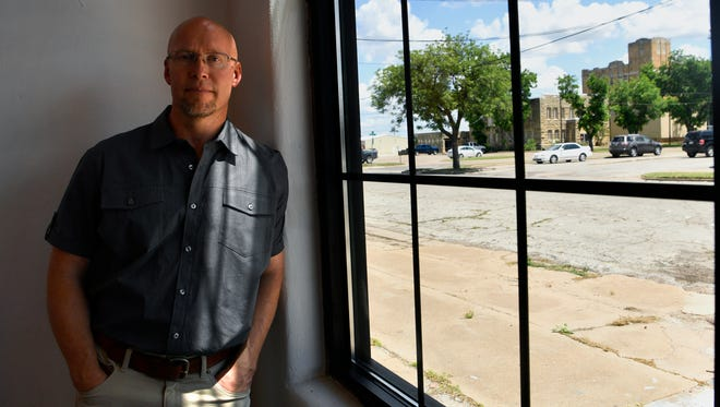 Developer Tim Smith stands beside a window at his SODA Courtyard with the unoccupied Welfare Building and former Taylor County Jail in the distance Wednesday. Smith wants the county to sell those buildings for development.
