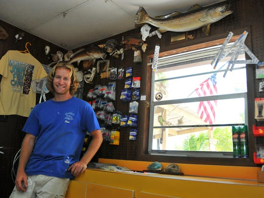 Honest John's Fish Camp in Melbourne Beach, established in 1880. Elliott Bedford stands in the shop at the camp, with the record trout displayed on the wall.