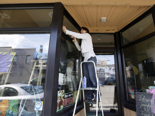 Laura Steger cleans the windows of her store, The Traveling