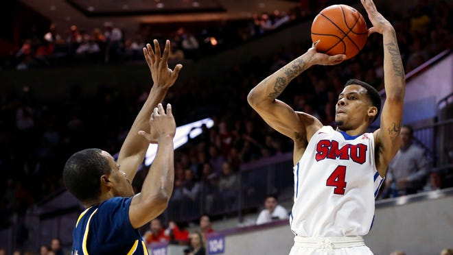 """FILE - In this Dec. 8, 2015, file photo, SMU guard Keith Frazier (4) shoots over Michigan guard Muhammad-Ali Abdur-Rahkman, left, during the second half of an NCAA college basketball game in Dallas. Frazier is transferring after taking time away from the undefeated No. 10 Mustangs to consider his future with the program. Coach Larry Brown said Friday, Jan. 15, 2016, that the former Dallas high school star and McDonald's All-American """"wanted a fresh start."""" (AP Photo/Jim Cowsert, File)"""