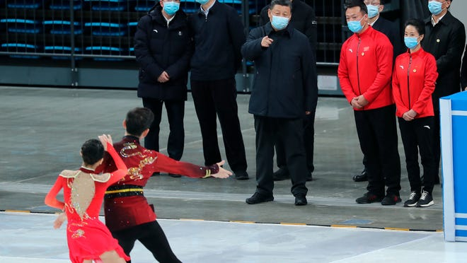 "FILE - In this Jan. 18, 2021, file photo released by China's Xinhua News Agency, Chinese President Xi Jinping, center, watches skaters perform during a tour of venues and preparations for the 2022 Beijing Winter Olympics at the Capital Gymnasium in Beijing. The 2022 Beijing Winter Olympics will open a year from now. Most of the venues have been completed as the Chinese capital becomes the first city to hold both the Winter and Summer Olympics. Beijing held the 2008 Summer Olympics. But these Olympics are presenting some major problems. They are already scarred by accusations of rights abuses including ""genocide""against more than 1 million Uighurs and other Muslim ethnic groups in western China. (Yao Dawei/Xinhua via AP, File)"
