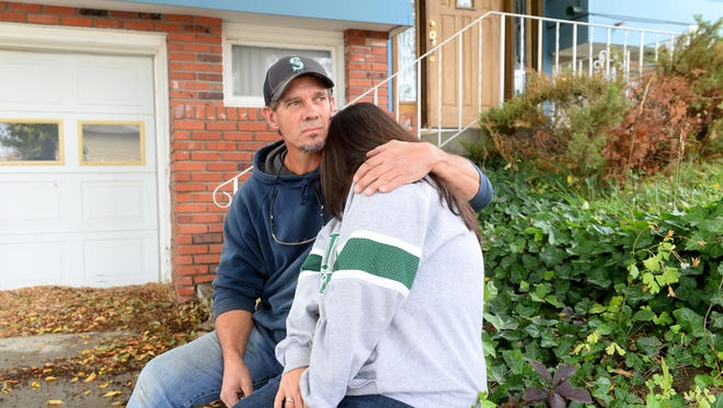 Tony Rucinsky comforts his wife, Ruth, while they talk about their struggles when their home was sold for back taxes.