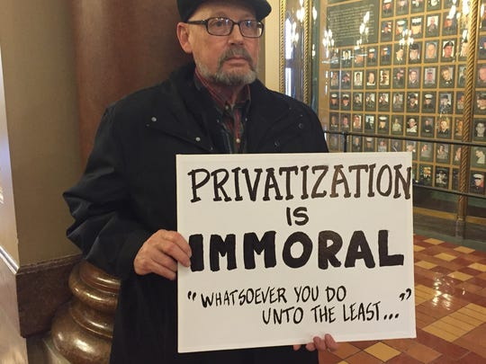 Eric Stimson of Des Moines holds a sign in the Iowa Capitol Rotunda Wednesday to protest plans to have private firms take over management of Iowa's Medicaid program.