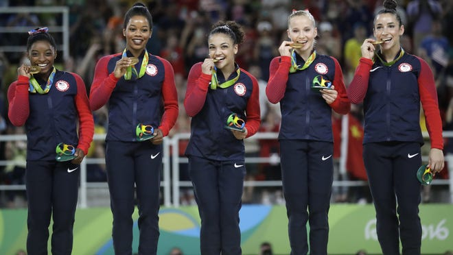 """U.S. gymnasts, from left, Simone Biles, Gabrielle """"Gabby"""" Douglas, Lauren Hernandez, Madison Kocian and Aly Raisman hold their gold medals during the medal ceremony for the artistic gymnastics women's team at the 2016 Summer Olympics on Aug. 9, 2016 in Rio de Janeiro, Brazil."""