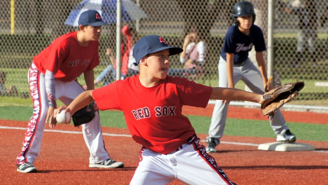 """Deming Little League action is well underway at E.J. Hooten Sports Complex. Teams play nightly on four diamonds at the park with boys and girls, ages 9-16 participating. The age-old rivalry between the Red Sox and the Yankees was renewed Tuesday when the """"Boys from Bean Town"""" defeated the """"Bronx Bombers"""" 7-1 in Major Division (ages 11-12) play. Red Sox pitcher Carlos Apodaca makes his delivery to the plate while first-baseman Alan Carreon holds Yankees runner Tristan Seats on the bag. On the girls softball diamond, Chloe Johnson delivers a shot to the outfield when the Pirates tangled with the Cubs in a Senior Division (13-16) matchup."""