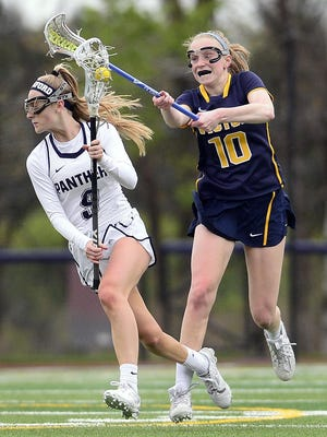 Pittsford's Jenna Doyle, left, eludes pressure from Victor's Caroline Wood. Doyle scored two goals during a game at Pittsford Sutherland on Friday. Pittsford beat Victor, 11-6.
