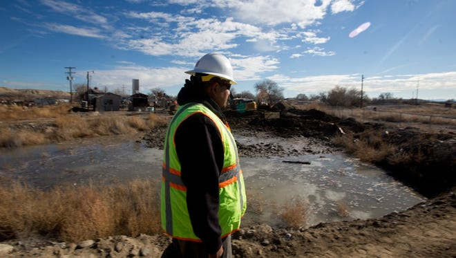 Gregory Bahe, a water and wastewater operations supervisor for Navajo Tribal Utility Authority's Engineering, Construction and Operations Division, provides a tour of the site where repair work on a ruptured wastewater pipeline is taking place in Shiprock.